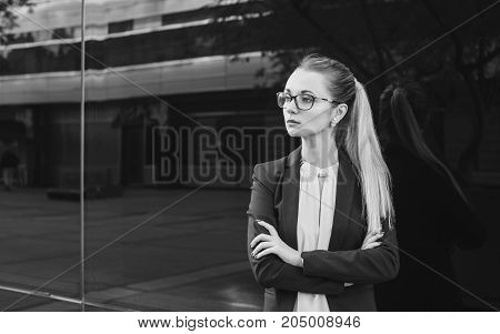 Serious young woman in suit and glasses business manager or teacher on dark background black and white