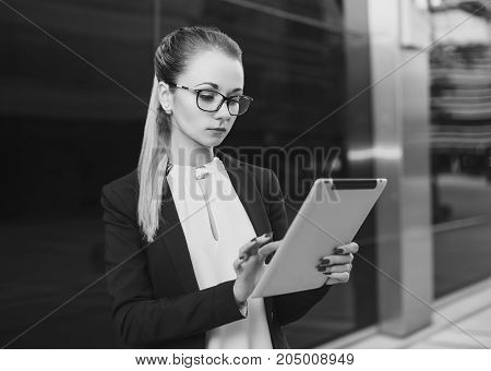 Beautiful woman in suit with glasses using a tablet. Business concept black and white