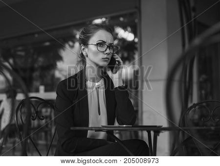 Serious business woman in elegant suit and glasses talking on the cellphone sitting in the outdoor cafe. Bad news. Black and white