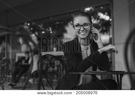 Happy business woman in suit with glasses sitting in the outdoors cafe and talking on the phone smiling. Copy space black and white