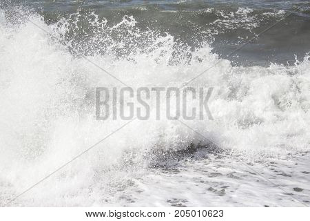 Powerful Waves Of The Sea Foaming, Breaking Against The Rocky Shore