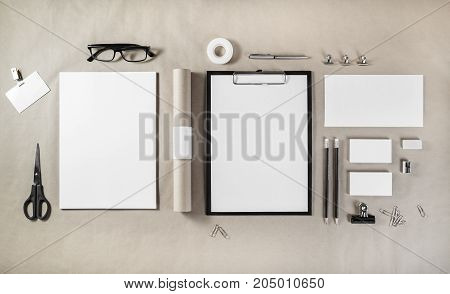 Photo of blank stationery set on craft paper background. Responsive design mockup for placing your design. ID template. Top view.