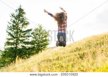 Freedom young woman jumping on mountain peak rock. Freedom enjoyment concept.