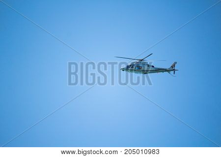 Helicopter Flying In The Blue Sky. Blue Background