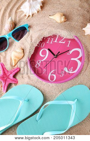 Pink clock immersed in sand with flips sunglasses and seashells