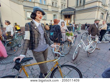 KYIV, UKRAINE - SEP 17, 2017: Young cute woman in vintage clothing ready for cycling on old bicycle at fashion festival Retro Cruise on June 17, 2017. Kiev is the 8th most populous city in Europe.