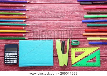 School supplies on the red wooden table