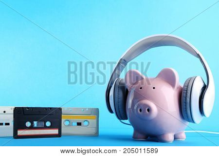 Headphones On Piggybank With Cassette Tapes On Wooden Table