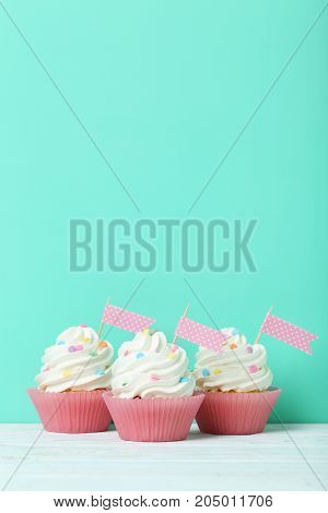 Tasty and sweet cupcakes on a green background
