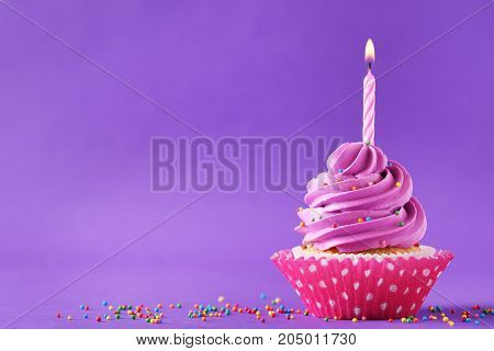 Tasty Cupcake With Candle On A Purple Background