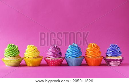 Tasty and sweet cupcakes on a pink background