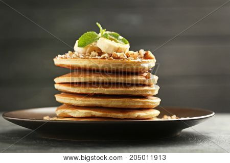 Tasty Pancakes With Walnuts And Bananas On Grey Wooden Plate