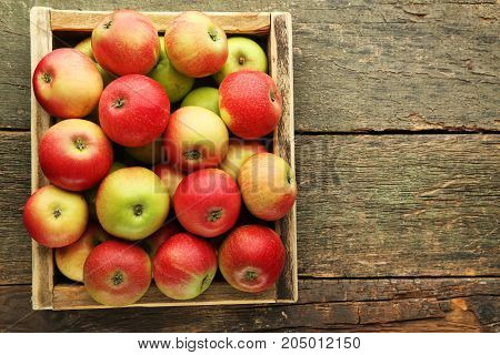 Ripe And Sweet Apples In Crate On Wooden Table