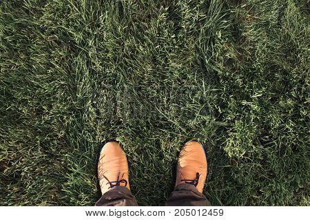 Beige suede boots on a green grass. Top view, outdoor flat lay. Space for text.
