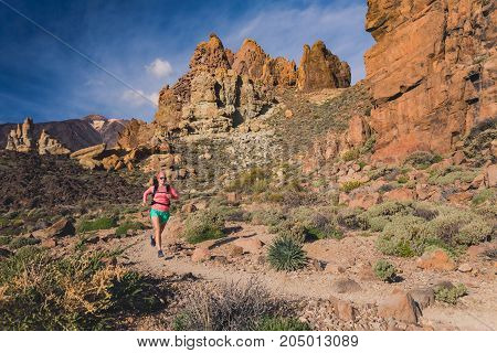 Young woman running in mountains on rocky trail. Cross country runner training in inspiring nature dirt footpath on Tenerife Canary Islands Spain.