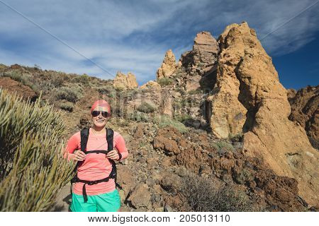 Happy girl hiker walking on mountain path. Inspire and motivate concept for outdoors activity. Female runner or climber looking at inspirational landscape on rocky trail on Tenerife Canary Islands