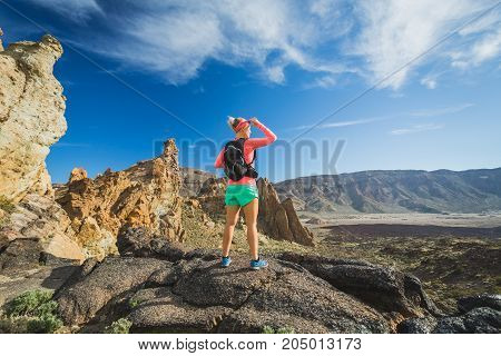 Woman hiker reached mountain top. Inspire and motivate concept for outdoors activity. Female runner or climber looking at inspirational landscape on rocky trail on Tenerife Canary Islands Spain.