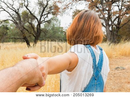 Young Girl Holding Man Hand in Brown Field