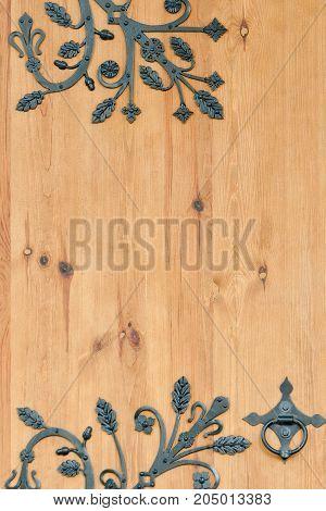 The wooden door with wrought metal elements