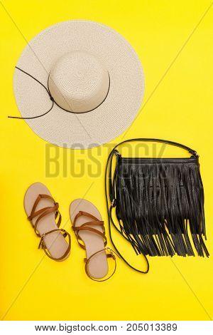 Fashionable concept. Women's beach hat handbag sandals. Yellow background