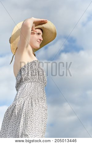 Beautiful Girl In Hat And Dress Looking Afar Against A Cloudy Blue Sky Background