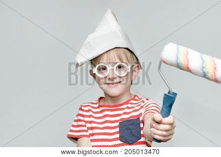Boy In A Paper Hat Is Playing In A Painter. Portrait. Roller For Painting