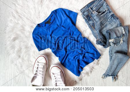 Blue T-shirt, Ripped Jeans And White Sneakers. Fashionable Concept On White Fur