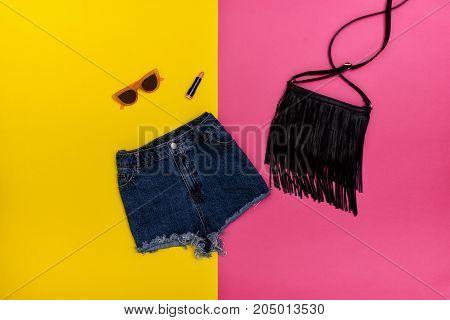 Denim Shorts, Black Handbag, Lipstick And Glasses. Bright Yellow And Pink Background. Fashionable Co