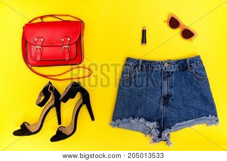 Denim Shorts, Black Shoes, Red Handbag And Glasses. Bright Yellow Background. Fashionable Concept