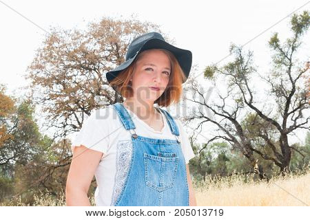 Beautiful Girl With Red Hair Overalls and Black Hat Standing in Field