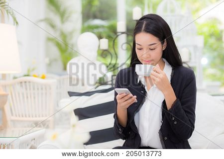 business - technology and people concept - happy young man with smartphone and coffee cup in living room.