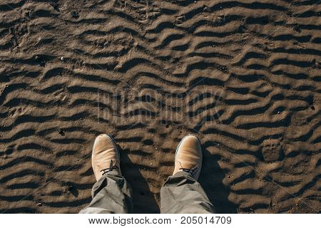 Top view of legs and beige suede boots standing on the beach