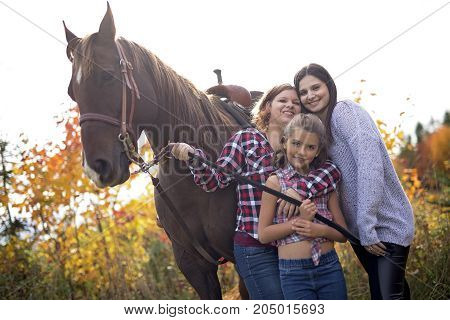 Two Beautiful and natural adult woman outdoors with horse and child