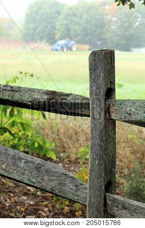 Split rail fence bordering a farm field on a foggy early fall day.