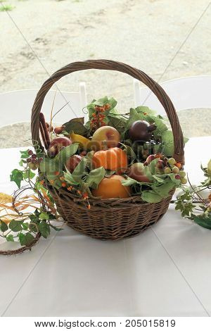 Basket of artificial fruits and vegetables displayed on a white tablecloth.