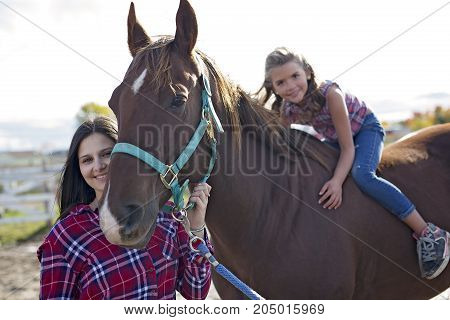 A Beautiful and natural adult woman outdoors with horse and child