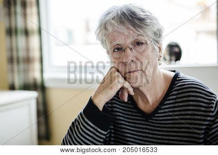 senior sitting near the window in the kitchen.