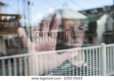 A Senior woman looking out through a window like depress