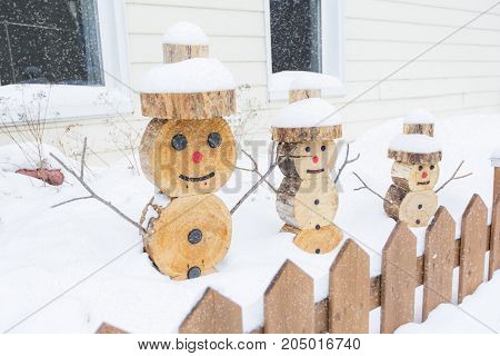 A snowman made in piece of wood with fence on the front