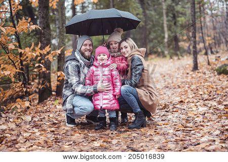 A family under umbrella in autumn city park, happy family
