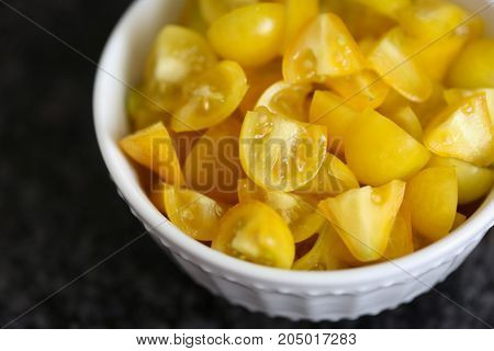 Bowl of chopped heirloom yellow pear tomatoes. Shallow depth of field.