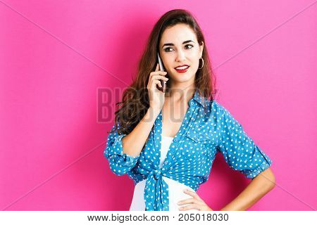 Young woman talking on the phone on a pink background