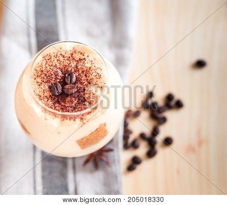 Tasty tiramisu dessert in glass, on wooden background