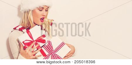 Happy young woman with Christmas present boxes on a white background