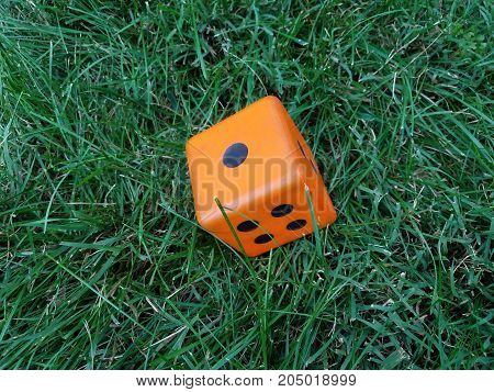 an orange dice with the numbers 1, 2, and 4 showing