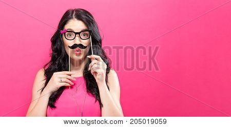 Young woman holding paper party sticks on a solid background