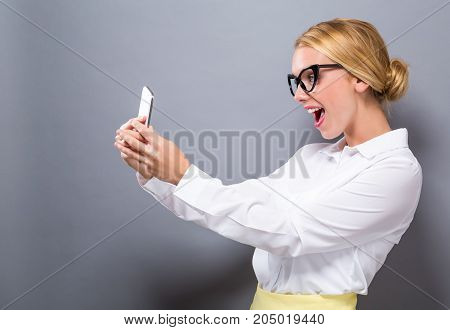 Young woman using her phone on a gray background