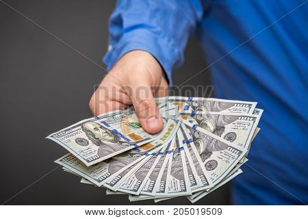 A man holding a fanned group of one hundred dollar bills