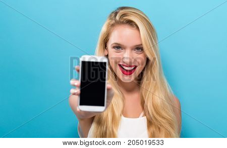 Young woman holding out a cellphone in her hand
