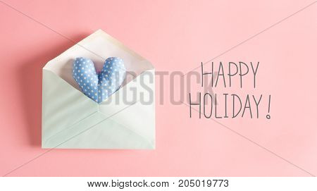 Happy Holiday message with a blue heart cushion in an envelope